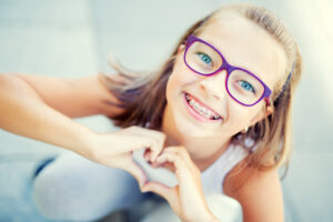 smiling girl with glasses and braces