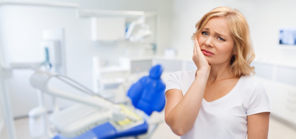 unhappy woman suffering toothache at dental office